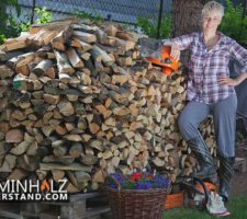 Frau vor einem Stapel Kaminholz