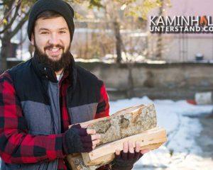 Mann im Winter im Schnee mit Kaminholz für seinen Kaminholzunterstand