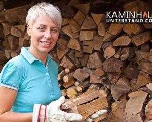 Frau mit Kaminholz vor Kaminholzunterstand