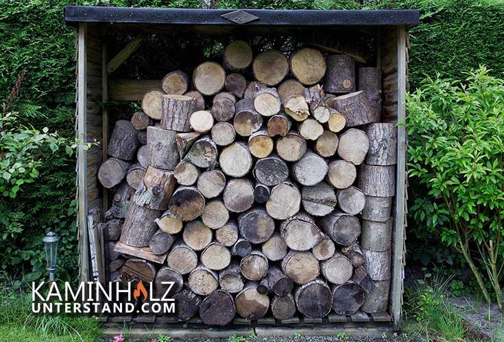 Kaminholzunterstand mit Brennscheiten im Garten - Die Firma Moorland bietet auch Kaminholzregale an.