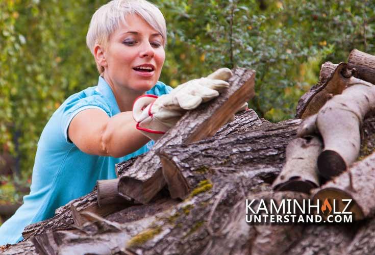junge Frau stapelt Holz in einen Kaminholzunterstand wie von Gartenpirat XXL